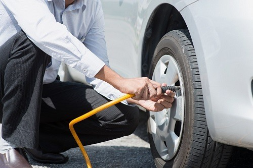 Man Pumping Tire With Inflator